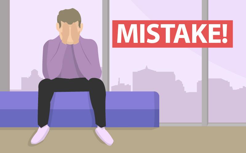 """Ein Mann sitzt und hält sich die Augen mit den Händen zu. Neben ihm steht das Wort """"Mistake"""" geschrieben."""